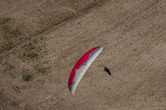Red and white paraglider pilot flying above the fields during co Stock Image