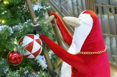 A red and white penguin climbs the stairs to the Christmas tree stock photos