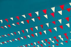 Red and White Pennant Flags. Seven diagonal strings of alternating orange red and white pennants against a steel blue sky Royalty Free Stock Images