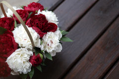 Peonies on wooden background. Red and white peonies on a wooden background in a basket royalty free stock image