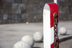 Red and white. Photo of a bollard of red and white colour with sunlight Stock Image