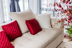 Red and white pillow on modern white sofa. At home Stock Photography