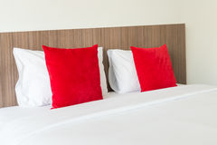 Red and white pillows on a bed.  Stock Images