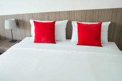 Red and white pillows on a bed.  Royalty Free Stock Photography