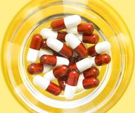 Red and white pills. Sit in a glass cup Royalty Free Stock Photo
