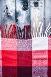 Red and white plaid with the fringe. Red and white plaid on a shabby wooden background Royalty Free Stock Photography