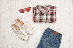 Red and white plaid shirt, glasses, sneakers and jeans. Wooden background. Fashionable concept, top view Stock Photo