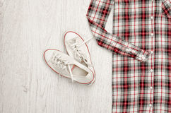 Red and white plaid shirt and sneakers. Wooden background. Fashi. Onable concept, top view Royalty Free Stock Photo