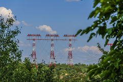 The red and white poles for energy transmission on the background of green forest royalty free stock photography