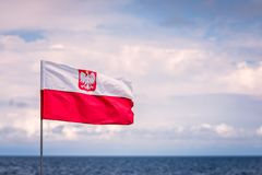 Red and white Polish flag. With national eagle emblem fluttering in the wind on a seaside stock photo