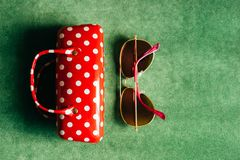 A red white polka-dot female glasses case and pink sunglasses