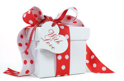 Red and white polka dot theme gift box present. With heart shape gift tag, with love, for Christmas, Valentine, birthday, wedding or special occasion Stock Photography