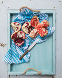 Red and white pomegranates with knife in blue tray over light painted wooden backdrop Royalty Free Stock Photo