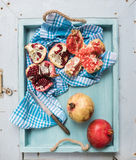 Red and white pomegranates with knife on kitchen towel in blue tray over light painted wooden backdrop Royalty Free Stock Photos