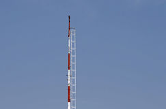 RED AND WHITE RADIO MAST AGAINST BLUE SKY Stock Photo