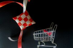 Red and white ribbon of ketupat and troly for shopping