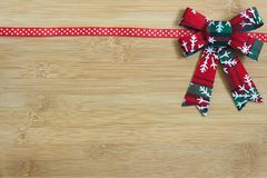 Red and white ribbon on light wood background with Christmas wreath decoration Stock Images
