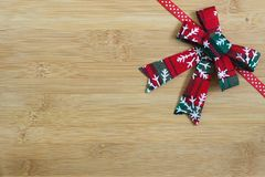 Red and white ribbon on light wood background with Christmas wreath decoration Stock Image