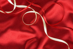 Red and white ribbon on a red silk Royalty Free Stock Photo