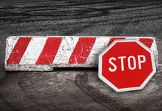 Red white road barrier and stop road sign Royalty Free Stock Photos