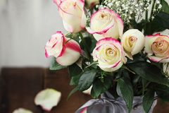Red and White Rose Bouguet in a Vase. Beautiful bouquet of  red and white roses with baby`s breath in a metal farmhouse style vase. Selective focus on roses in Stock Photography
