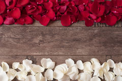 Red and white rose petals on the wooden background. Rose Petals Border on a wooden table. Top view, copy space. Floral frame. Styled marketing photography Stock Photography