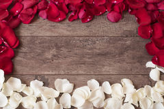 Red and white rose petals on the wooden background. Rose Petals Border on a wooden table. Top view, copy space. Floral frame. Stock Photos