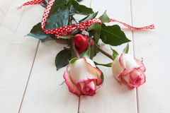 Red and white roses tied with at ribbon and hearts. On painted wood Royalty Free Stock Photography