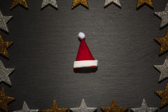 Red and white santa hat on slate with star frame Stock Photo