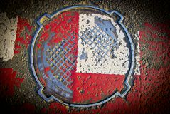 Red white sewer hatch with rubbed paint. Close up Stock Photo