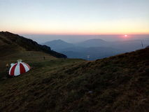 White and red shelter on a mountain ridge during sunrise. Red and white shelter at sunrise, on a mountain ridge Stock Images