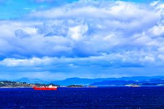 Red and white ship at sea, the mountains in the background Stock Photo