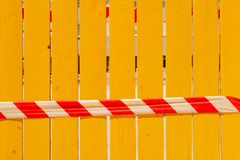 A red and white signal tape against a yellow fence. royalty free stock image