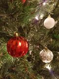 Red and white and silver Christmas ball decorations. Gold Christmas ball decorations hanging on a Christmas tree with some red ribbon Stock Photography