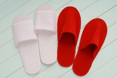 Red and white slippers from hotel, red and white slippers from a. Irplane are on white wooden floor, home slippers are on white background, home footwear Stock Photo