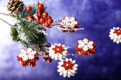 Red with white snowflakes and Christmas branch with berries. Royalty Free Stock Photo