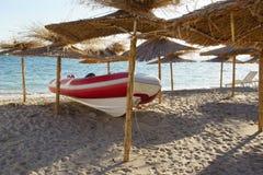 Red White SpeedBoat Under Beach Umbrella Stock Image