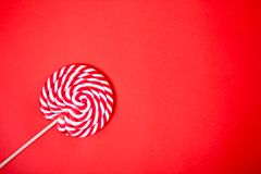 Red and white spiral lollipop. Red and white spirals on lollipop. Colorful candy on coral background. Space for text, flat lay. Children, holiday, sweets royalty free stock images