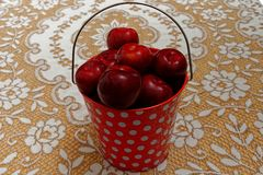 A red and white spotted pail full of bright red plums stock photos