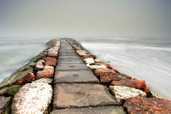 Red and white stone pier in the mist Stock Images