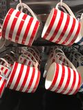 Red and white stripe mugs hanging on display in grocery store Stock Photography