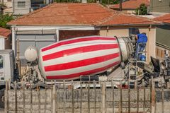 Red and white striped cement mixer truck with a man working at the rear of the truck. Starting the delivery of cement. Limassol, Cyprus - April 3, 2018: Red and royalty free stock image