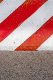 Red and white striped concrete road barrier on asphalt. Red and white striped concrete road barrier on asphalt - close up stock images