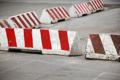 Red and white striped concrete road barriers Stock Images