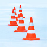 Red and white striped cones on ice Royalty Free Stock Photos