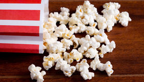 Red white striped container box lying tipped over on wooden surface with popcorn spread out Stock Image
