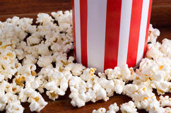 Red white striped container box lying tipped over on wooden surface with popcorn spread out Royalty Free Stock Image
