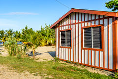 Red & white striped house on Caribbean beach Royalty Free Stock Images