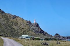The red and white striped lighthouse at Cape Palliser on North Island, New Zealand stands high on the cliffs. The light was built stock photography