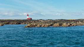 Red and white striped lighthouse on remote rocky island. A red and white striped islands marking one of the Seal islands in Farne Isles, England Royalty Free Stock Images